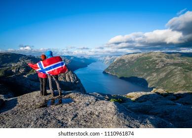 View on Lysefjord fjord from the Preikestolen pathway. Couple of tourists with the flag of Norway