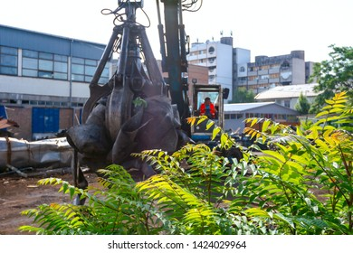 View on machine, loader manipulator with hydraulic grappling claw until is collecting, moving old steel, scrap metal.