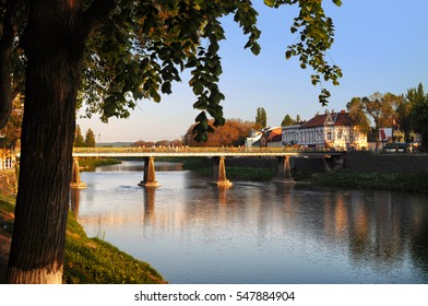 View on the main bridge across the river Uzh in Uzhhorod in warm sunset light. High green tree growing nearby, its branches hanging over the river