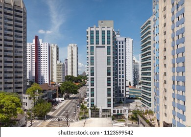 View on main road with modern high rise skyscraper buildings in São Paulo neighbourhood of Santo Amaro in Brazil against a blue sky