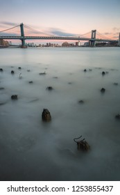 View on Manhattan bridge from broken pier at sunset with long exposure