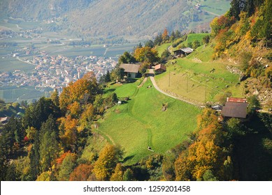 View on meadows and cottages in the italian alps near Meran, South Tyrol, Italy. In the distance the village Partschins