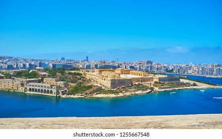 The view on the medieval star fort on Manoel Island and the modern coast of Gzira and Sliema resorts behind it from the top of St Michael's Bastion of Valletta fortress, Malta.