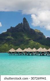 view on Mount Otemanu through turquoise lagoon and overwater bungalows on the tropical island Bora Bora, honeymoon destination, near Tahiti, French Polynesia, Pacific ocean