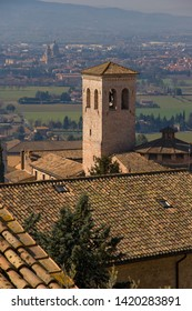View on Museo di San Pietro from above roof in medieval pilgrimage town Assisi in Italy, birthplace of saint Francis and Clare of Assisi, with old stone houses with flowers in flower pots on walls