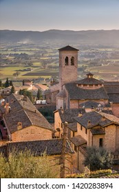 View on Museo di San Pietro from above roof in medieval pilgrimage town Assisi in Italy, birthplace of saint Francis and Clare of Assisi, with old stone houses with flowers in flower pots on walls A
