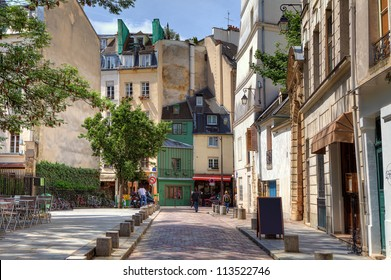 View on narrow cobbled street among traditional parisian buildings in Paris, France.