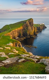 View on the Neist Point Light House with rocky cliff-top overlooking a causeway, lit by sunset glow, during golden hour, taken from the Neist Point trail, Waterstein, Isle of Skye, Scotland, UK