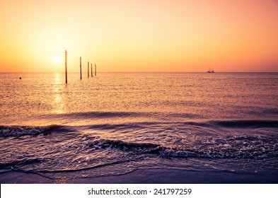 View on the North Sea with sunset and a fishing ship near the horizon from the Sankt Peter-Ording beach.