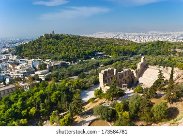 The view on the Odeon of Herodes Atticus - a stone theatre, located on the slope of Acropolis with the Philopappos Hill on the background, Athens, Greece.