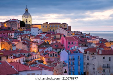 View on the old town Alfama in Lisbon, Portugal, in the very early morning with the street lights still burning, rich gradation of colorful houses ranging from blue  to pink and the dome of a church