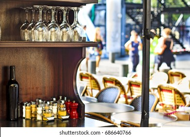 View on the parisian cafe from the counter. On the foregorund a wooden furniture containing mustard bottles and salt and papper shakers. On the defocused background cafe chairs and tables.