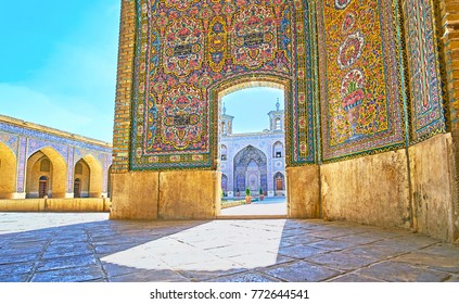 The view on portal with minarets and arched gallery of Nasir Ol-Molk mosque through the doorway of its summer hall, Shiraz, Iran.