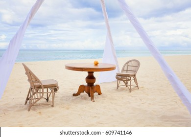 View on private dining table and wicker chairs for romantic dinner for honeymoon  couples on a tropical beach