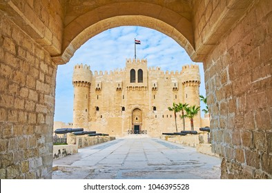 The view on the Qaitbay Fort through its entrance stone gate, the alley with cannons is seen on foreground, Alexandria, Egypt.