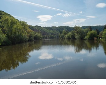 view on river Berounka from pedestrial bridge from village Zadni Treban to Hlasna treban in central Bohemian region, green lush trees reflecting in water, blue sky, spring sunny day