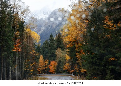 View on road in autumnal forest through windscreen of moving car. Rainy weather, raindrops on windshield.