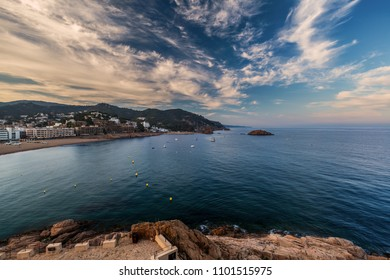 View on rock with viewer site in front and small marine town near mountains and sea bay in distance under cloudy sky at sunset in Costa Brava (Spain)