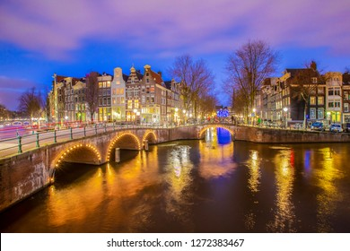 View on romantic canal Leidsegracht in Amsterdam at night with city lights, bridges and reflection on water