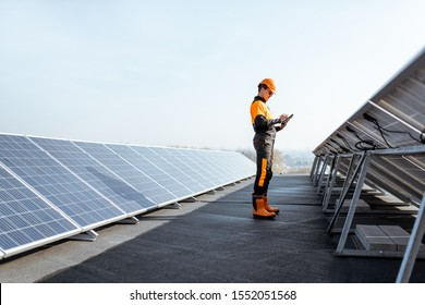 View on the rooftop solar power plant with engineer in protective workwear walking and examining photovoltaic panels. Concept of alternative energy and its maintenance