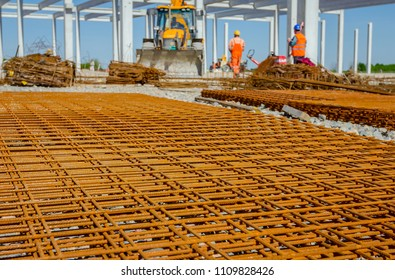 View on rusty square reinforcement for concrete, construction site is in background.
