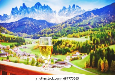 View on Santa Maddalena - St. Magdalena village, Odle - Gaisler mountain massif, Dolomite Alps, South Tyrol, Italy. Glass of beer on hotel balcony tray. Hello and welcome to Italian alps background.