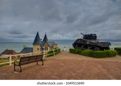 The view on sea with wooden bench and a tank in historic town Arromanches in France, where allies in world war landed