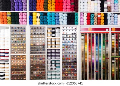 view on sewing shop shelves with various knitting yarn, buttons, threads and other supplies