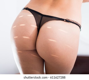 view on sexy female buttocks in panties in sunbeam lights