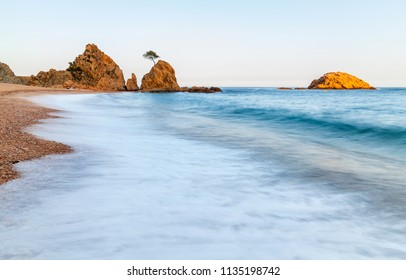 View on small shingle beach with blurred sea waves in front and few rocks in distance under clean sky at sunset in Costa Brava (Spain)