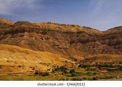 view on small village in front of massive red cliff