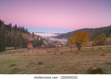 View on the small village in the mountains at sunrise with fog