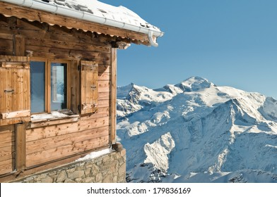 view on a snowy mountain and blue sky from a cottage