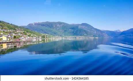 A view on the Songefjorden (King of the Fjords) from the water level. It is the deepest fjord in Norway. Tall, lush green mountains surrounding the fjord. Wavy surface of the water. Clear blue sky.