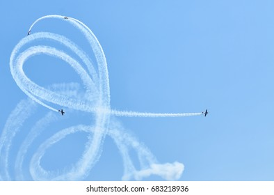 View on sport plane vapour trail in shape of spiral. White vapour trail track on blue sky background. Sport plane Aerobatic maneuver stunt. Spinning plane vapour trail in the sky.