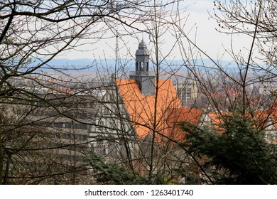 view on a steeple and roof through the branches at the sparrenburg in bielefeld germany photographed during a sightseeing tour at a sunny day