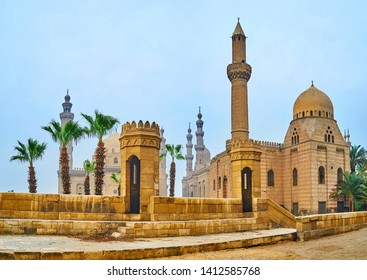 The view on the stone guard towers of Bab Al-Azab gate of Saladin Citadel and the tall minarets of great historic mosques of Sultan Hassan, Al-Rifa'i, Al-Mahmoudia, Cairo, Egypt