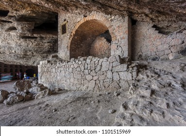 View on stony square with standing people in rocky cave with overhanging ceiling, pile of stones and stone stage in center lit with diffused sunlight in Crimea