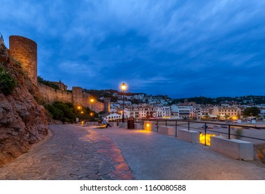 View on street with benches and street lights,handrail in right,ancient fortress with battlement wall on rock in left and small marine town under cloudy sky in distance at dusk in Costa Brava (Spain)