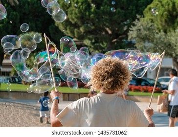 View on street performer blowing soap bubbles outdoor. Young artist entertains tourists on the street in summer. Funny caucasian man with blond curly hair makes big colorful soap bubbles.
