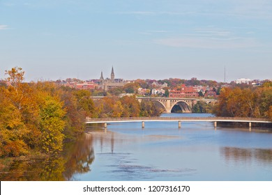 A view on suburban Washington DC in autumn with university buildings and bridges across Potomac River. Urban landscape on early morning with reflection in quiet river waters, Washington DC, USA.