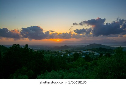 view on the sunset with yellow orange colours with dark clouds and sun rays in the blue sky background above the sea and mountains from the Zia village Greece in the Kos island