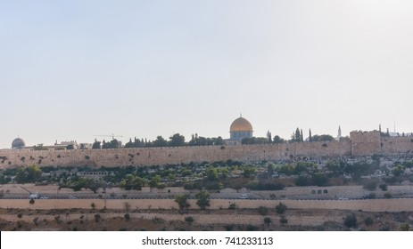 View on Temple Mount with Dome of the Rock Mosque behind Old City brick wall from Mount of Olives. Jerusalem, Israel.
