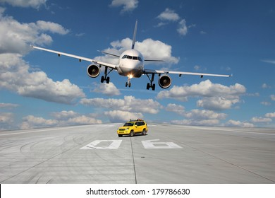 View on the threshold of runway 06 with follow me car and a passing plane