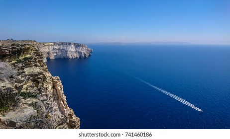 View on top of Gozo Cliffs, boat crossing sea, Malta