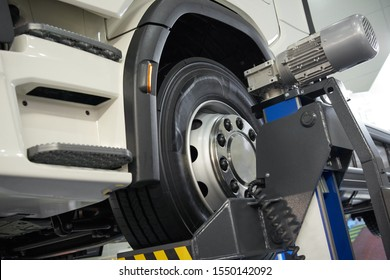 View on truck chassis front axle with wheel on maintenance electric lift. Truck workshop equipment and tools for car and vehicle truck maintenance and repair. Car under inspection on elevator