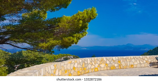 View on the turquoise blue sea and the bright green mediterranean pine from view point decorated with sand color stones, hot sunny morning on island Mljet, high season, Croatia
