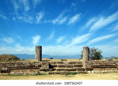 View on two ancient columns, remnants of staircase and big blue sky (with some clouds) in the background. Taken at the Monte Alban archeological site near Oaxaca (Mexico).