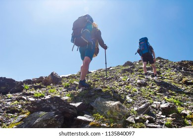 View on two climbers hike mount to peak of mountain. Leisure activity in mountains. Hiking sport in Svaneti, Georgia. Climbing. Tourists with backpacks on rocky hillside. Hikers on mountain trek
