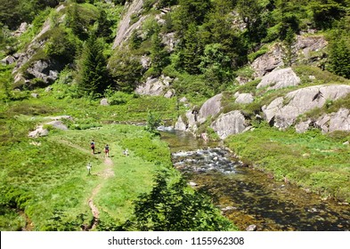 View on two hikers walking along the river on the GR10 trail in the Pyrenees, France